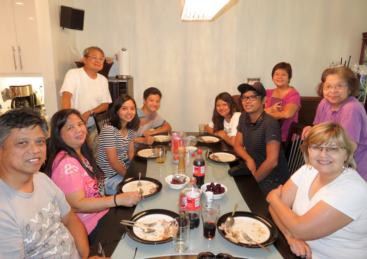 "The classic ""Filipino family eating at the table"" shot. Seated (left to right): Tito Noel; Tita Nora; cousins Rebeka, Dominic, and Laura; brother Rexis, and Tita Jennifer. Standing (left to right): Papa, Tita Marite, and Mama."